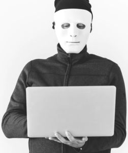 man in a mask holding a laptop
