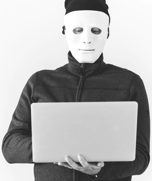 Man in a mask holding a laptop computer