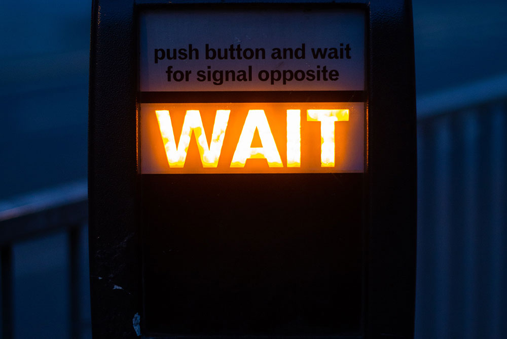 WAIT sign on British road crossing
